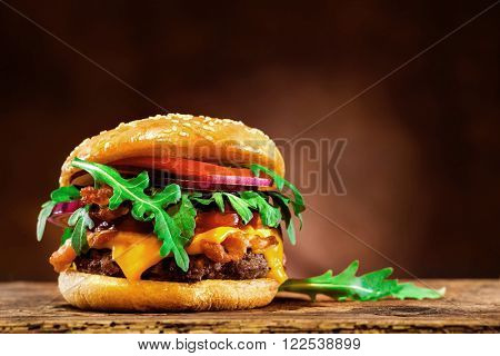 Delicious hamburger with rucola on wooden table