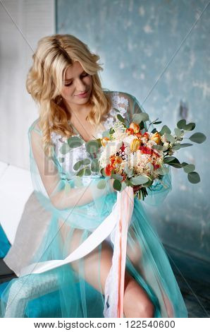 Bridal morning boudoir with smiling charming blond woman wearing mint transparent peignoir and holding fresh flowers ** Note: Shallow depth of field