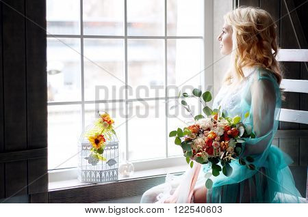 Bridal morning boudoir with smiling charming blond woman wearing mint transparent peignoir and holding fresh flowers
