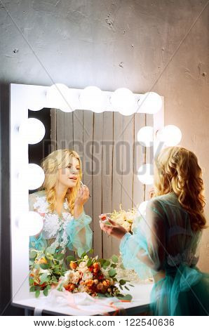 Evening boudoir. Blond woman doing her makeup at the dressing table.