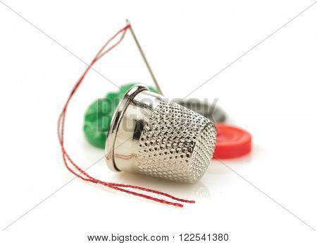 sewing thimble and thread with needle isolated on white background