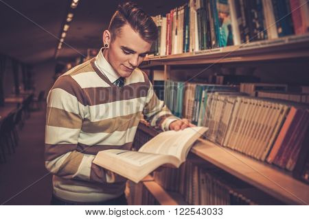 Attractive young man reading a book in the university library.