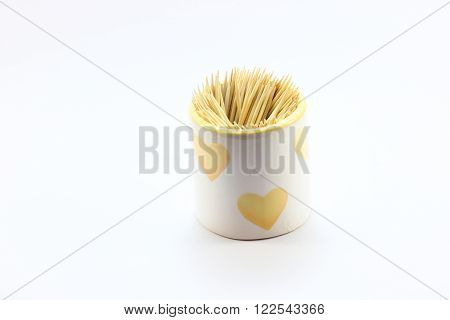A toothpick inserted in the cup brought by a white heart. On a white background
