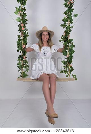 Beautiful young leggy blonde in a little white dress and white cowboy hat on a swing, wooden swing suspended from a rope hemp, rope wrapped vine and ivy.