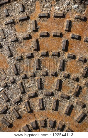 Relief pattern of rusty manhole cover in closeup.