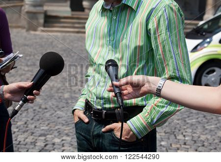 Reporters holding microphones conducting TV or radio interview