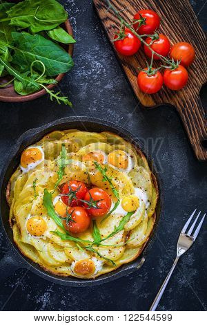 Breakfast potato frittata with spinach, arugula, cherry tomatoes and cheese in skillet on dark textured background, table top view food