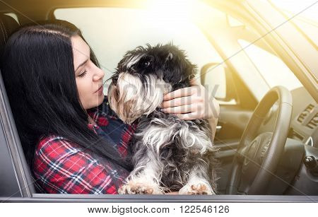 Young grl sitting in the car with her lovely dog