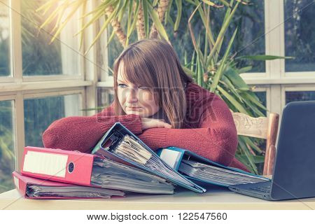 Overworked caucasian young woman is sitting at an office desk. Her hands are resting on folders lying in front of her and she is looking out of the camera. Photo is edited as instagram effect with light in the upper left edge.