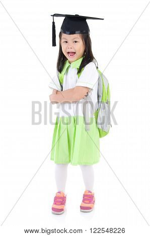 Asian primary student carried school bag and wearing mortarboard isolated on white background