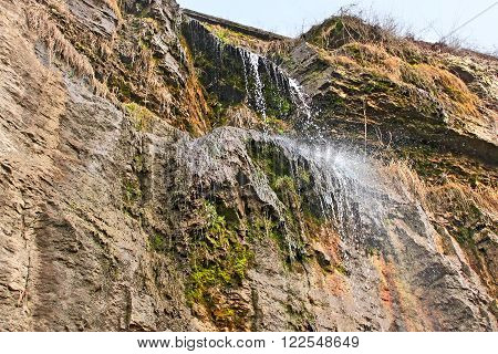 High waterfall on a vertical rock with a small amount of water in Kamianets-Podilskyi Ukraine