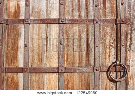Fragment of restoring medieval wooden gate with iron details