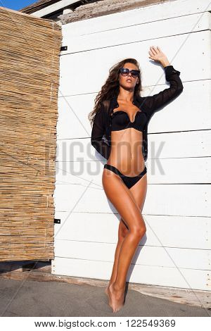 tanned attractive young woman in black bikini and shirt in front of white wooden background on beach sunny summer day, full body shot