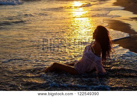 young woman sit at sand beach in sea water at sunset, full body shot side view
