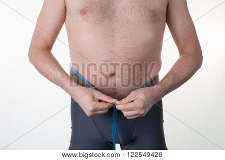 Cropped view of caucasian man measuring waist with tape.