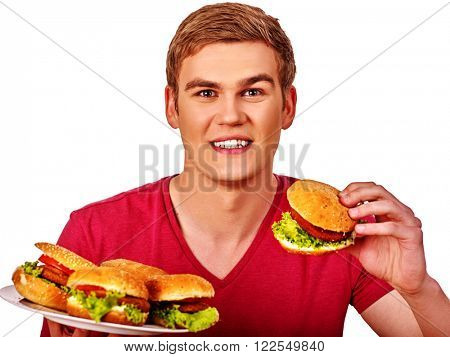 Young man keeps and eating a lot of big hamburgers. Fastfood concept.