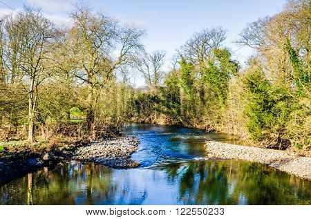 Reflections in water of River Kent at Levens Bridge in Cumbria, England on sunny day with blue skies.