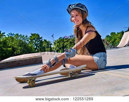 Sport girl with injury sitting near her skateboard and touching ankle outdoor.