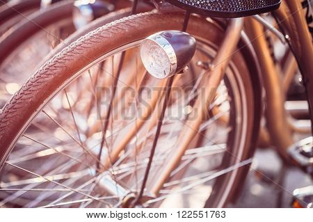 Close Up Of Wheel Of Bicycles On Parking In European City. Sunlight Sunshine Through Spokes Of Wheel. Close Up Of Bike Headlight, Lamp In Bokeh Background.