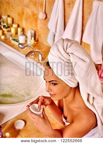 Woman relaxing at home luxury bath. Girl put cream on face. Face cosmetic.