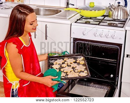 Young blond smilig woman bake cookies. She puts cookies in oven kitchen.