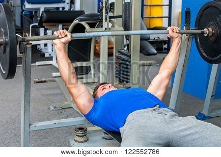 Sport man working his arms and back at sport gym. He lying on bench and lifting barbell.
