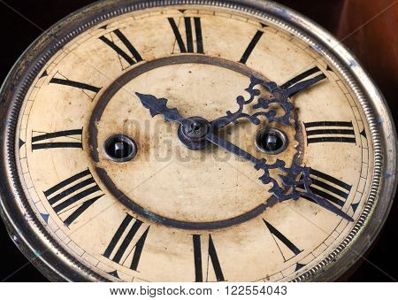 Vintage wall clock on a dark background closeup