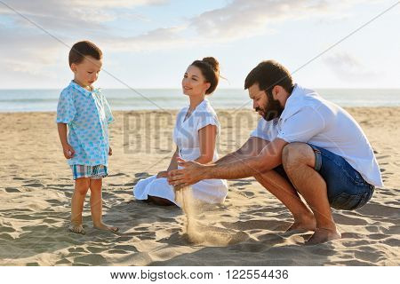 Happy family - mother father and small baby son sit on sunset sea beach and play with sand slipping through man hand fingers. Active parents and people outdoor activity on summer vacations with child