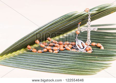 Closeup of Holy Catholic rosary with crucifix and beads on palm leaf