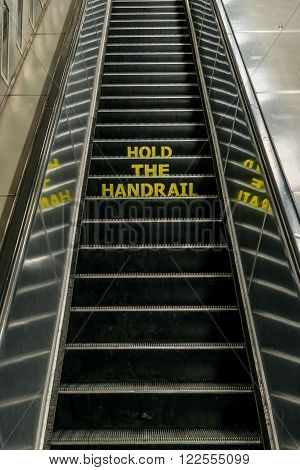 London United Kingdom - March 20 2016: Hold the Handrail notice on an escalator in London Underground Euston Station