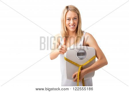 Woman with tape measure and weight scale showing thumbs up