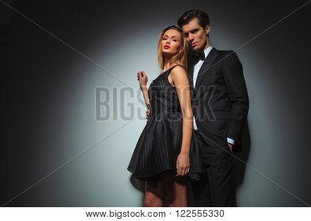 businessman in black standing with hand in pocket while embracing woman in black dress from behind. woman raised one hand while looking at the camera in gray studio background