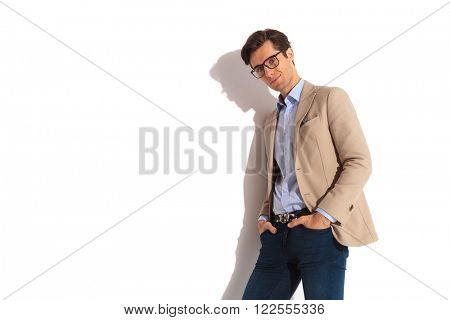 portrait of smart casual man leaning on the wall with both hands in pockets while posing for the camera in isolated studio background