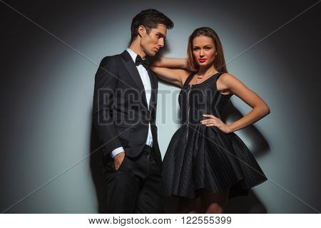 elegant couple in black posing. the man is standing with hands in pockets looking at the woman while the woman with one hand on waist and one hand on his shoulder is looking at the camera.