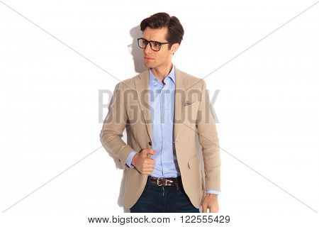 portrait of handsome casual man wearing glasses and fixing his jacket while posing looking away from the camera in isolated studio background