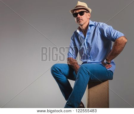 portrait of mature man in jeans wearing hat and sunglasses while seated with hand on waist. the man is looking away from the camera in gray studio background.