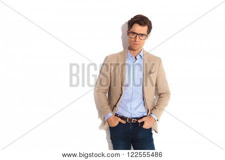portrait of adult wearing jeans and glasses while posing looking at the camera with both hands in pockets in isolated studio background.