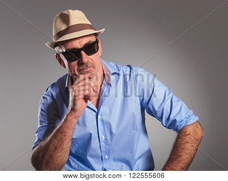 closeup portrait of mature man in open shirt thinking and looking away from the camera. the man is wearing brown hat and black sunglasses in gray studio background.