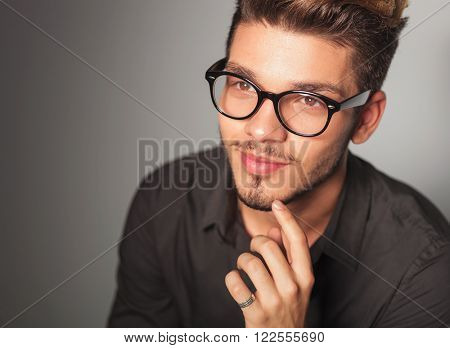 smiling young man dreaming about something, looking up in studio with hand his chin