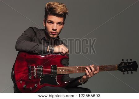 side view of a young man holding an electric guitar and looks away from the camera