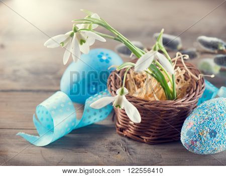 Easter Concept. Art design with colorful blue eggs and spring snowdrop flowers over wooden Background. Beautiful Easter holiday greeting card with decorated handmade eggs and spring flowers
