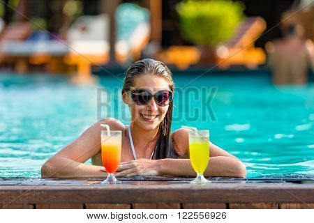 Brunette girl with cocktails relaxing in swimming pool, hotel resort on background
