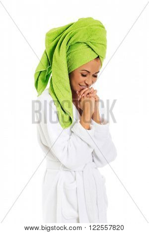 Laughing woman in bathrobe clenching hands