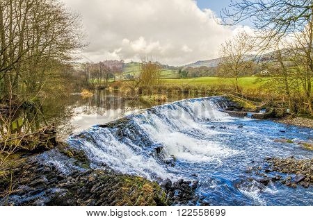 Weir on River Kent at Staveley in Cumbria, England on sunny day.