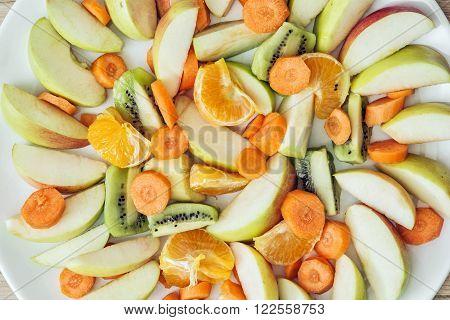 Sliced carrots, apple, kiwi, tangerine and oranges. Fruit theme. Healthy food.