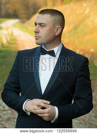Handsome stylish young bridegroom in black wedding suit jacket white shirt on bow tie standing outdoor in forest on natural background vertical picture