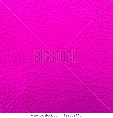 Bright pink bumpy painted wall texture close up in square format.