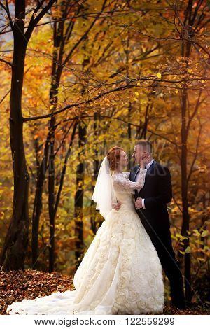 Young wedding romantic couple of bride in white dress and bridegroom in suit standing in autumn deep forest outdoor on natural background, vertical picture