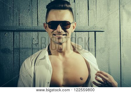 One cool amazing sensual positive young boy brunet in black sunglasses unbutton white shirt having muscular beautiful chest looking straight posing on gray wooden backdrop studio, horizontal picture