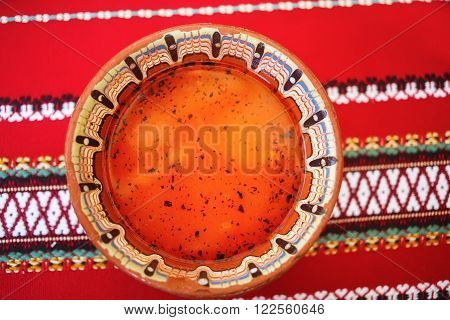 A plate of soup on a background of bright red tablecloths. Plate with traditional Bulgarian ornament filled with spicy soup. Soup in the restaurant. Bulgarian food. Shallow depth of field. Selective focus.